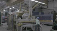 Workers using machines in glass factory Stock Footage