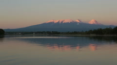 Sunset lighting Kluchevskaya group of volcanoes with reflection in river Stock Footage