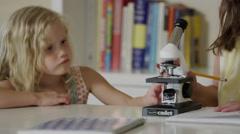 Close up of girls using microscope and writing notes / Orem, Utah, United States Stock Footage