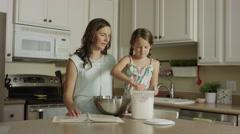 Medium panning shot of mother watching daughter scoop flour into bowl / Orem, Stock Footage