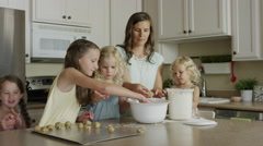 Medium panning shot of mother and daughters rolling cookie dough / Orem, Utah, Stock Footage