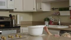 Medium panning shot of girl taking cookie dough from bowl in kitchen / Orem, Stock Footage