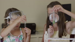 Close up panning shot of girls examining test tubes with magnifying glass / Stock Footage