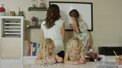 Medium panning shot of mother home schooling daughters / Orem, Utah, United Stock Footage