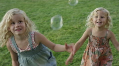 Close up panning shot of girls chasing bubbles outdoors / Orem, Utah, United Stock Footage