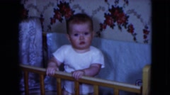 1951: baby stands in crib holding railing and showing emotions while moving Stock Footage