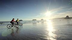 Young couple mountain biking on Pacific ocean beach, Oregon Stock Footage
