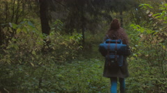 TRACKING FOLLOW  Caucasian woman with a backpack hiking in autumn forest Stock Footage