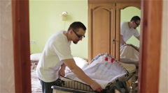 Young dad prepared a cot for a newborn in a bedroom. Father pleased. Stock Footage