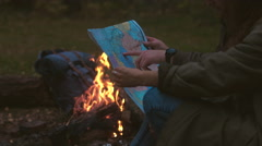 CINEMAGRAPH - Hikers couple studying the map near bonfire Stock Footage