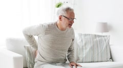 Unhappy senior man suffering from backache at home 104 Stock Footage