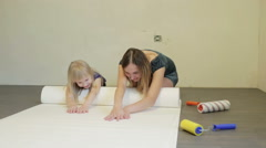 Mother and little blonde daughter are smoothing a white wallpaper on the floor. Stock Footage