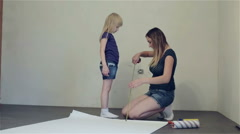 Mother is measuring daughter's height with tape or roulette during repairs. Stock Footage