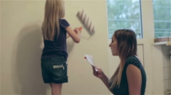 Mom reads the instructions and teaches her daughter to hang wallpaper. Stock Footage