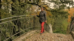 A woman walks in the park, going through the old bridge, sunny autumn day Stock Footage