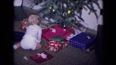1969: a girl and her baby brother grabbing the presents for christmas NEW YORK Stock Footage