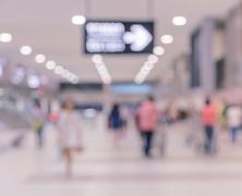 Blurred passengers in airport arrival terminal background Kuvituskuvat