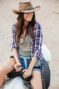 Happy pretty young woman cowgirl riding a horse outdoors Stock Photos
