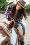Cheerful woman cowgirl enjoying riding horse in village Stock Photos