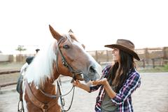 Cheerful woman cowgirl playing with horse in countryside Stock Photos