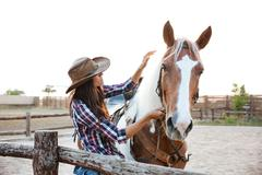 Beautiful young woman cowgirl with horse in village Stock Photos