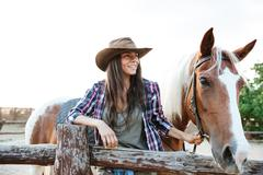 Smilng woman cowgirl standing with her horse on ranch Stock Photos