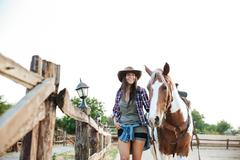 Happy beautiful young woman cowgirl with her horse on ranch Stock Photos