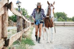 Woman cowgirl in hat walking with her horse in village Stock Photos