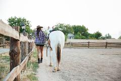 Back view of woman cowgirl walking with horse Stock Photos