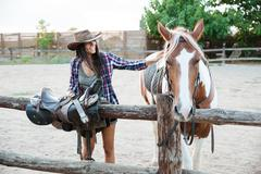 Smiling woman cowgirl taking care of horse and preparing saddle Stock Photos