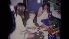 1969: a family unwrapping gifts underneath a christmas tree NEW YORK Stock Footage