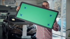 Man in Car Dealership Holding Green Sign Stock Footage