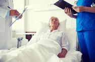 Doctor and nurse visiting senior woman at hospital Stock Photos