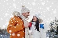 Happy couple with tea cups over winter landscape Stock Photos