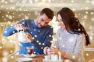 Happy couple drinking tea at cafe Stock Photos