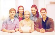 Smiling students with tablet pc at school Stock Photos
