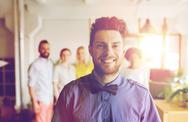 Happy young man over creative team in office Stock Photos