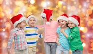 Happy little children in santa hats hugging Stock Photos