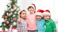 Happy little children in christmas santa hats Stock Photos