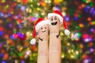 Close up of two fingers with smiley and santa hats Stock Photos
