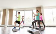 Group of people exercising on steppers in gym Stock Photos