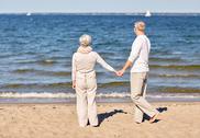 Happy senior couple holding hands summer beach Stock Photos