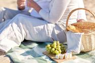 Happy senior couple having picnic on summer beach Stock Photos