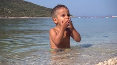 Child sneezes and washes up in the sea Stock Footage