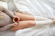 Close up of woman with tea cup in bed Stock Photos