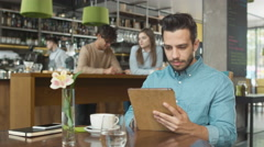 Hispanic Ethnicity Young Man using Tablet Computer at Cozy Coffee Shop. Stock Footage