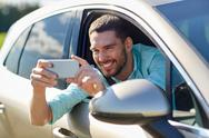 Happy smiling man with smartphone driving in car Stock Photos