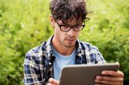 Man in glasses with tablet pc computer outdoors Stock Photos