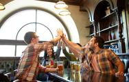 Friends with beer making high five at bar or pub Stock Photos