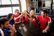 Football fans clinking beer glasses at sport bar Stock Photos